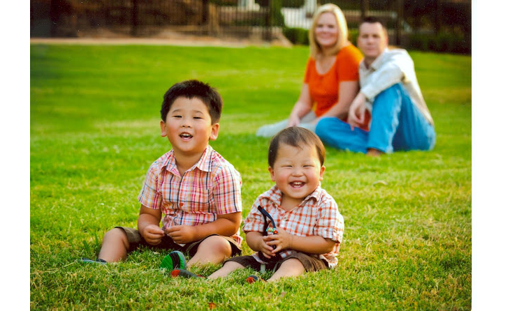 Two smiling adopted children sitting in front of their parents on a lawn