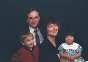 Parents with two kids in front of black backdrop